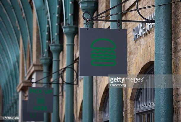 A logo hangs on a sign outside Shake Shack's new burger restaurant in London UK on Tuesday July 2 2013 Shake Shack opening in London's Covent Garden...