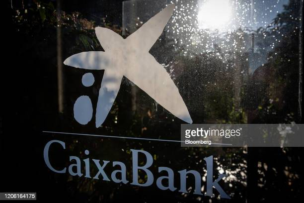 A logo is displayed at the entrance to the headquarters of CaixaBank SA in Barcelona Spain on Thursday March 5 2020 Spanish bank shares soared after...