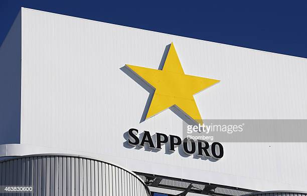 A logo is displayed atop of raw material tanks at the The Sapporo Breweries Ltd factory in Eniwa Hokkaido Japan on Monday Feb 17 2015 The factory...