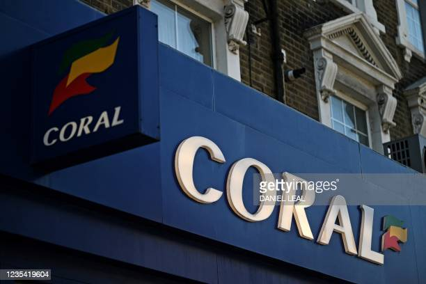 Logo is pictured on a sign above the entrance to a Coral betting shop in east London on September 22, 2021. - UK gambling giant Entain said on...
