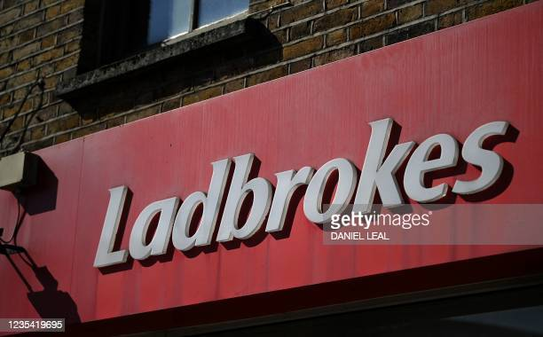 Logo is pictured on a sign above the entrance to a Ladbrokes betting shop in east London on September 22, 2021. - UK gambling giant Entain said on...