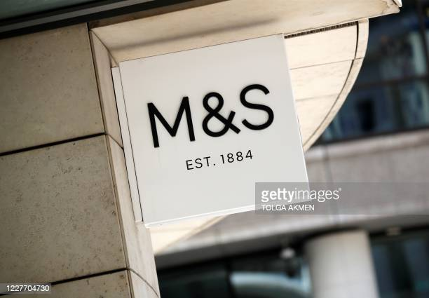 Logo is pictured on a sign outside an M&S store in central London on July 20, 2020. - British clothing-to-food retailer Marks & Spencer could axe up...