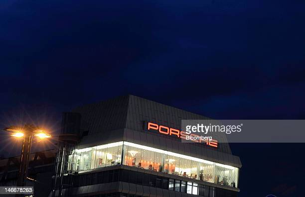 A logo is seen illuminated above the Porsche AG plant in Stuttgart Germany on Thursday June 21 2012 Porsche AG which is jointly owned by Volkswagen...