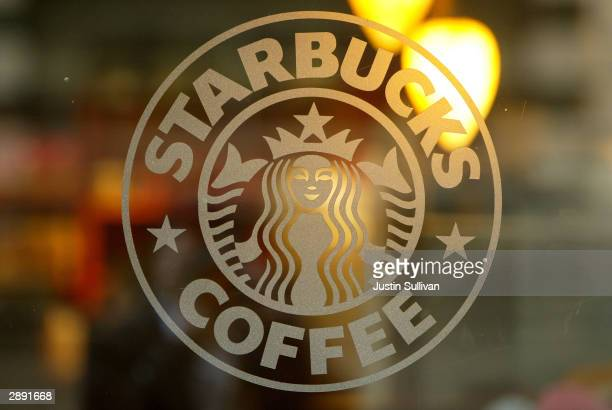 A logo is seen on the glass storefront door of a Starbucks coffee shop on January 22 2004 in San Francisco California The Starbucks Corporation on...