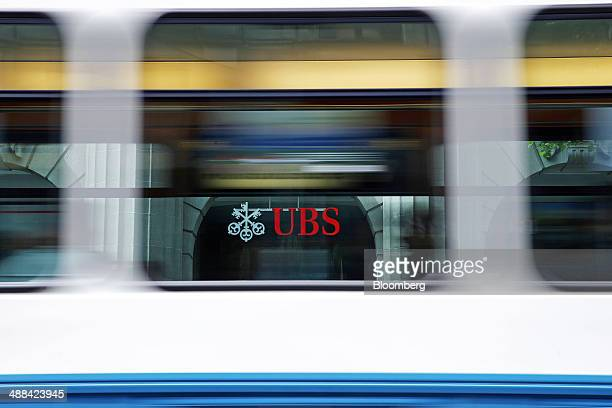 A UBS logo is seen through the carriage windows of a commuter tram as it passes headquarters of UBS AG in Zurich Switzerland on Tuesday May 6 2014...