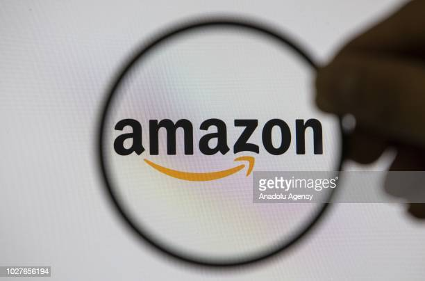 Logo of 'Amazon' online shopping website is seen inside a circle held by a person in front of a screen in Ankara Turkey on September 06 2018