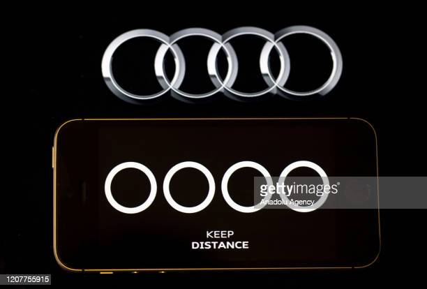 Logo of Audi, German Automobile Company, and a phone screen with Audi's social distancing message with the separated rings to point out the...