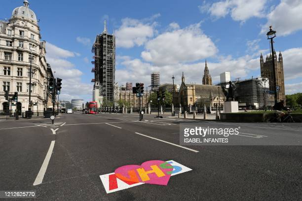 A logo of Britain's NHS is pictured on an empty road near the Houses of Parliament in central London on May 11 as life in Britain continues during...