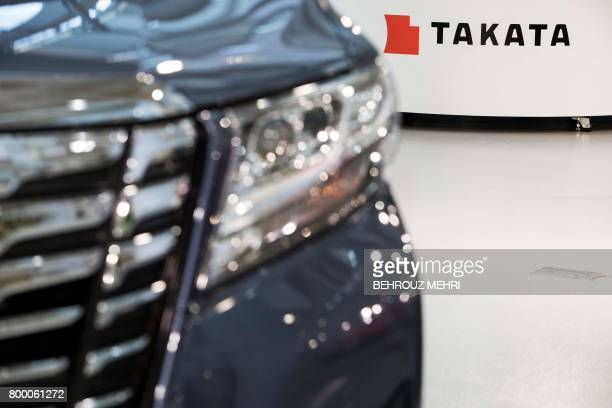 Logo of the Japanese auto parts maker Takata is seen next to a car at a showroom in Tokyo on June 23 2017 Takata shares swung wildly rebounding by 45...