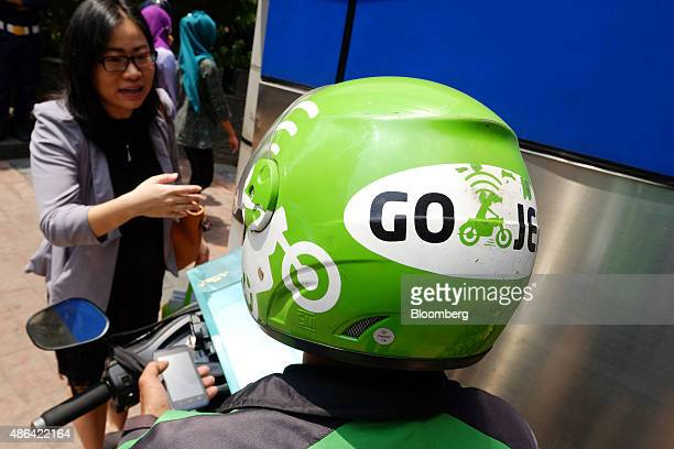 A logo of transport service GoJek is displayed on the helmet of one of the company's motorcycle riders as he speaks to a customer in Jakarta...