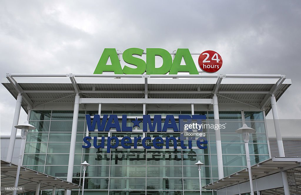 A logo sits above the entrance to an Asda supermarket, the U.K. retail arm of Wal-Mart Stores Inc., in Watford, U.K., on Thursday, Oct. 17, 2013. U.K. retail sales rose more than economists forecast in September as an increase in furniture demand led a rebound from a slump the previous month. Photographer: Simon Dawson/Bloomberg via Getty Images