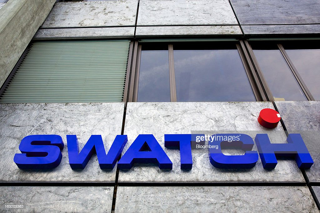 A logo sits above the entrance to the headquarters of Swatch AG in Bienne, Switzerland, on Wednesday, March 6, 2013. Swatch Group AG, the biggest maker of Swiss timepieces, fell as much as 3.1 percent in Zurich trading after Chief Executive Officer Nick Hayek sought to downplay expectations over industry growth prospects. Photographer: Gianluca Colla/Bloomberg via Getty Images
