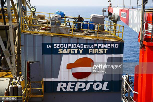 A logo sits beneath a safety first sign on the Casablanca oil platform operated by Repsol SA in the Mediterranean Sea off the coast of Tarragona...