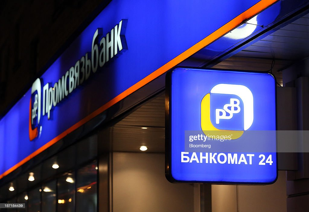 A logo sits illuminated above a sign for an automated teller machine (ATM) outside a branch of OAO Promsvyazbank in Moscow, Russia, on Wednesday, Nov. 28, 2012. Bank Rossii proposes government create rule limiting increases of budget funds held at central bank, RIA Novosti reports, citing First Deputy Chairman Alexey Ulyukayev. Photographer: Andrey Rudakov/Bloomberg via Getty Images
