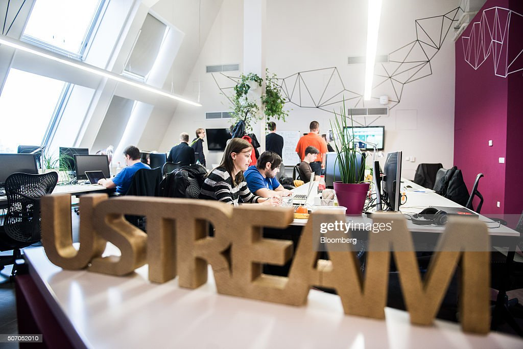 A logo sits on a desk area as employees work at laptop computers beyond, inside the Ustream, Inc. office in Budapest, Hungary, on Tuesday, Jan. 26, 2016. International Business Machines Corporation (IBM) is buying live video stream provider Ustream to help sell more video services to clients including the National Football League, HBO and the Food Network, through its cloud platform. Photographer: Akos Stiller/Bloomberg via Getty Images