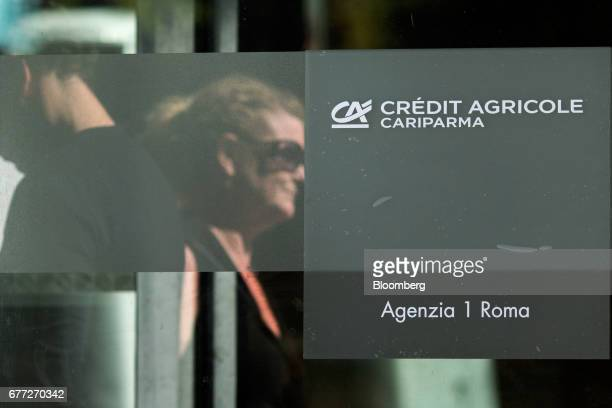 Logo sits on a glass panel outside a branch of Credit Agricole SA's Cariparma bank in Rome, Italy, on Tuesday, May 2, 2017. Cariparma is in...