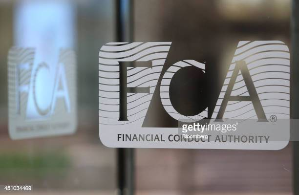 A logo sits on a revolving glass door at the headquarters of Financial Conduct Authority in the Canary Wharf business district in London UK on...