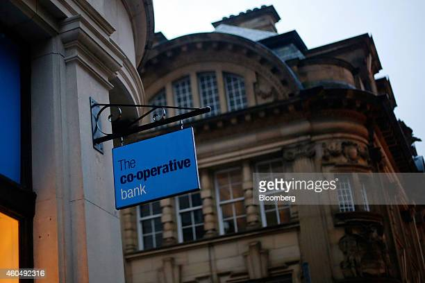 A logo sits on a sign above the entrance to a CoOperative Bank Plc branch a unit of CoOperative Group Ltd at dusk in Manchester UK on Sunday Dec 14...