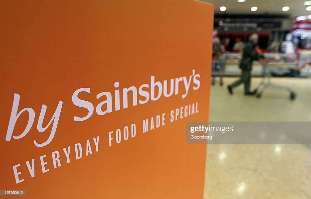 A logo sits on a sign as customers browse for goods inside a Sainsbury's supermarket store, operated by J Sainsbury Plc, in Godalming, U.K., on Thursday, May 2, 2013. J Sainsbury Plc, the U.K.'s third-largest supermarket chain, will report full year results on May 8. Photographer: Chris Ratcliffe/Bloomberg via Getty Images