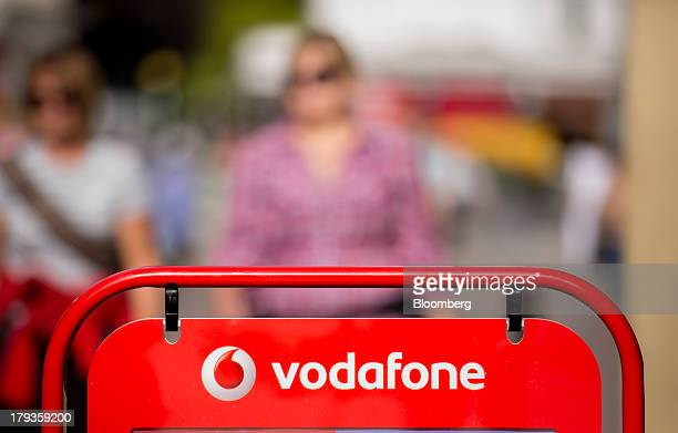 A logo sits on a sign outside a Vodafone store operated by Vodafone Group Plc in London UK on Monday Sept 2 2013 Verizon Communications Inc is poised...