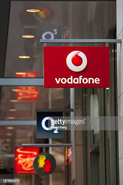 A logo sits on a sign outside a Vodafone store operated by Vodafone Group Plc beyond a logo for the mobile operator O2 part of Telefonica SA in...