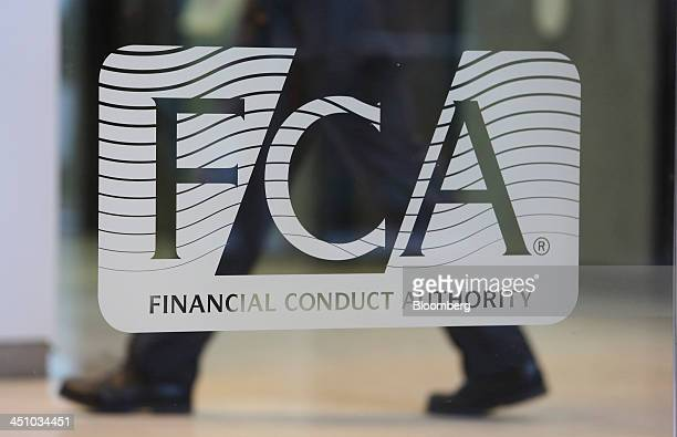 A logo sits on a window in the reception area of the headquarters of the Financial Conduct Authority in the Canary Wharf business district in London...