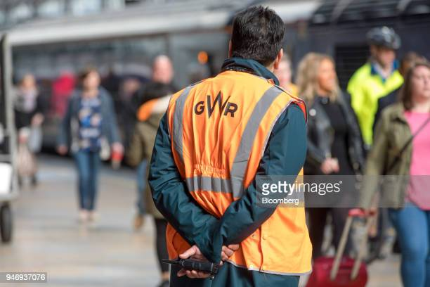 A logo sits on the back of a member of staff as he stands near a Great Western Railways train service operated by FirstGroup Plc at London Paddington...