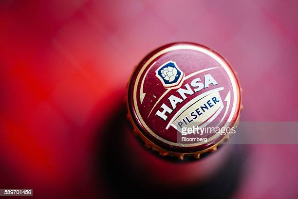 A logo sits on the cap of a Hansa Pilsener beer bottle in this arranged photograph at SABMiller Plc's brewhouse in the Sandton district of...