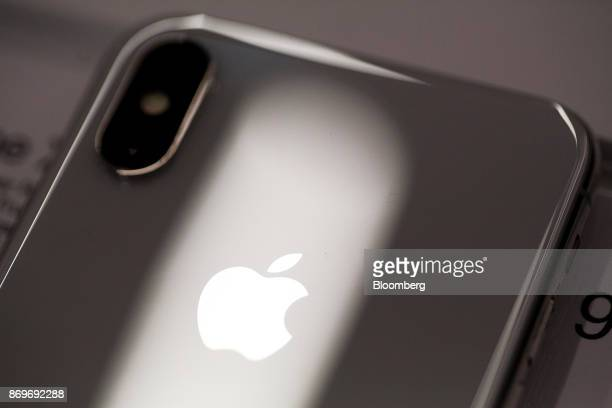 A logo sits on the case of an iPhone X smartphone on the first day of sale Customers queue at a reStore Apple Inc retailer in Moscow Russia on Friday...