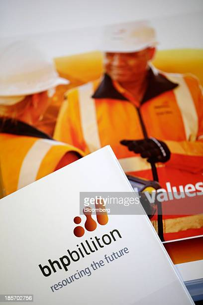 A logo sits on the cover of a brochure during BHP Billiton Ltd's annual general meeting in London UK on Thursday Oct 24 2013 BHP listed in Sydney and...