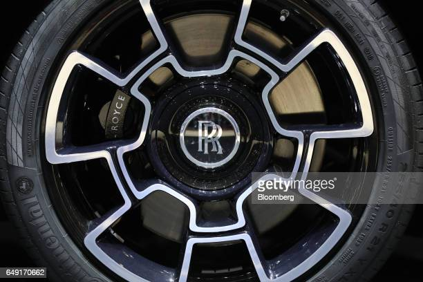 A logo sits on the hubcap of a RollsRoyce luxury automobile produced by Bayerische Motoren Werke AG as it stands on display on the first day of the...
