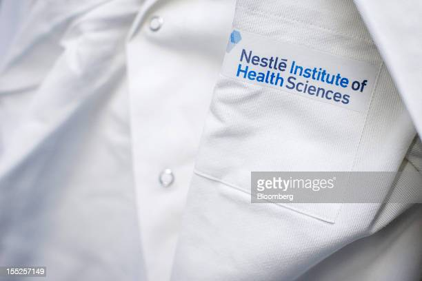 A logo sits on the pocket of a technician's lab coat during a DNA sequencing experiment in a laboratory inside Nestle SA's Institute of Health...