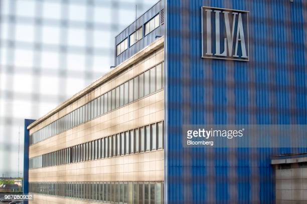 A logo sits on the side of a building at the Ilva SpA steel plant in Taranto Italy on Tuesday May 22 2018 TheIlva SpAsteel plant is twice the size...
