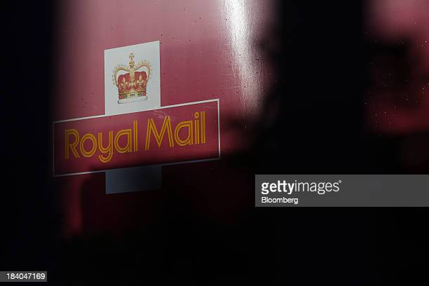 A logo sits on the side of a Royal Mail Group Ltd delivery truck at the company's postal sorting office in Romford UK on Friday Oct 11 2013 Royal...