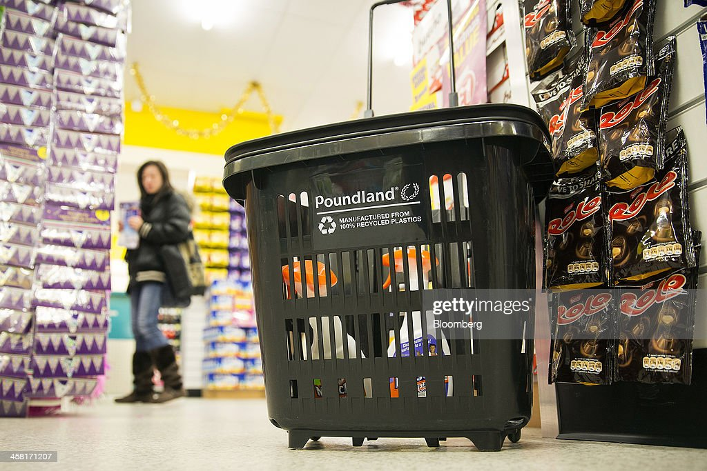 A logo sits on the side of a shopping basket as a customers browses goods inside a Poundland discount store, operated by Poundland Holdings Ltd., in Birmingham, U.K., on Friday, Dec. 20, 2013. U.K. discount retailer Poundland has hired Rothschild to manage its IPO, according to the Sunday Times newspaper. Photographer: Simon Dawson/Bloomberg via Getty Images