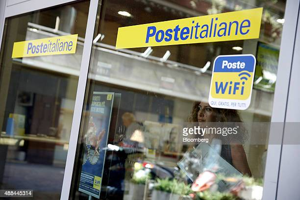 A logo sits on the window of a Poste Italiane SpA post office in Rome Italy on Tuesday Sept 15 2015 Italy is proceeding with a plan to sell as much...