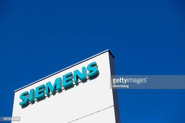 A logo stands outside the Siemens AG gas turbine factory in Berlin Germany on Monday Sept 30 2013 Siemens AG's new Chief Executive Officer Joe Kaeser...