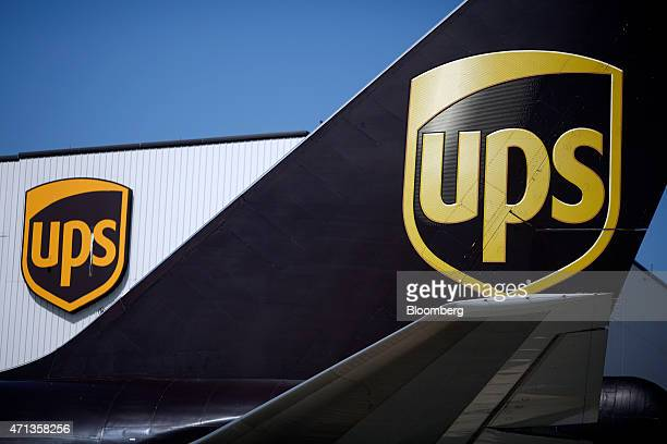 UPS logos are displayed on the tail of a Boeing Co 747 cargo jet and a maintenance hangar at the United Parcel Service Inc Worldport facility in...
