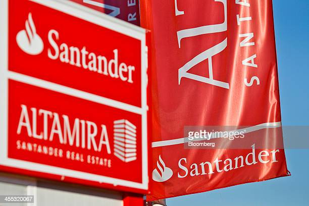 Logos for Altamira Banco Santander SA's real estate unit sit on display outside the sales office at the Jardines de la Condesa development in Madrid...