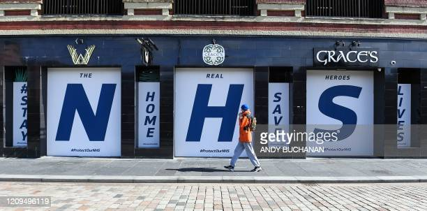 Logos of Britain's National Health Service , placed in the windows of a closed-down pub, in appreciation of the NHS's frontline medical staff working...