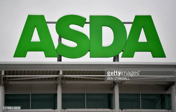 Logos of supermarket chain Asda are pictured on the handles of shopping trolleys outside a store in Ashford, south east England on October 2, 2020. -...