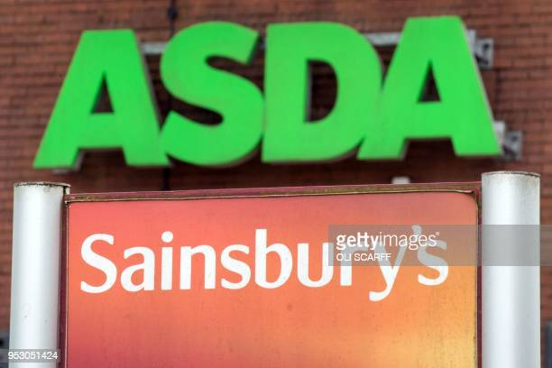 Logos of supermarket chains Asda and Sainsbury's are pictured outside adjacent branches of their stores in Stockport northern England on April 30...