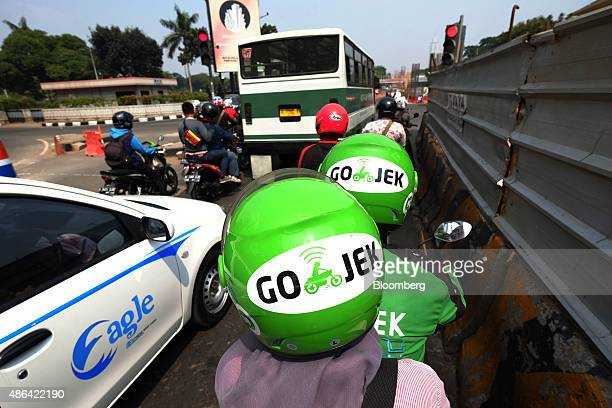 Logos of transport service GoJek logos are displayed on the helmets of one of the company's motorcycle riders and his passenger as they sit at a...