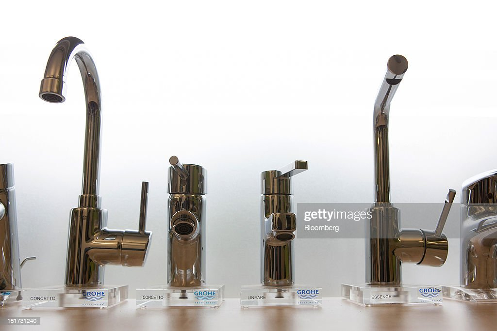 Logos sit beneath a display of bathroom taps, manufactured by Grohe Group, inside a bathroom store in Berlin, Germany, on Tuesday, Sept. 24, 2013. Lixil Corp., a Japanese toilet maker, is in advanced talks to buy German bathroom-fixtures company Grohe Group for more than 3 billion euros ($4 billion), according to people with knowledge of the matter. Photographer: Krisztian Bocsi/Bloomberg via Getty Images