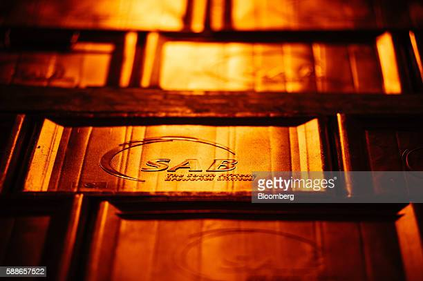 Logos sit illuminated on the side of beer storage crates in the distribution center at SABMiller Plc's Newlands brewery in Cape Town South Africa on...