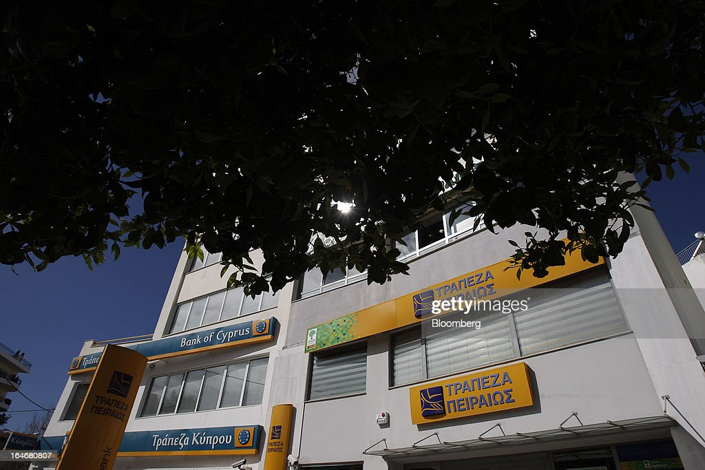 Logos sit on display above closed branches of Piraeus Bank SA, right, and Bank of Cyprus Plc, left, in Athens, Greece, on Tuesday, March 26, 2013. Piraeus Bank SA acquires Greek units of Cypriot lenders for total cash consideration of EU524m, according to e-mailed statement from the Athens-based lender today. Photographer: Kostas Tsironis/Bloomberg via Getty Images