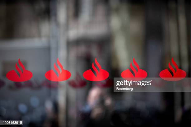 Logos sit on display on a window outside a Banco Santander SA bank branch in Barcelona Spain on Friday March 6 2020 Spanish bank shares soared after...