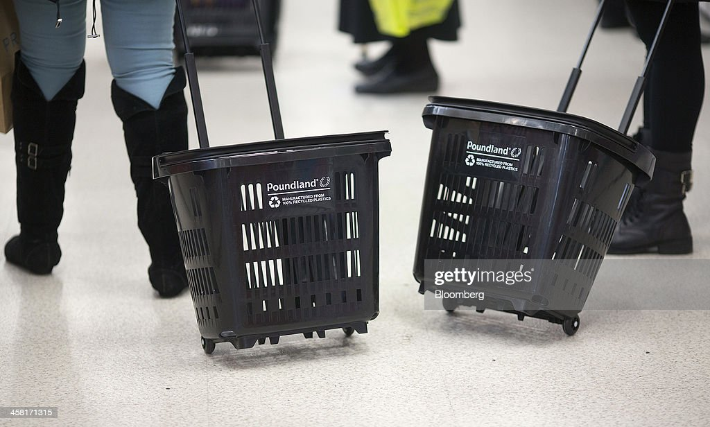 Logos sit on the side of a shopping baskets as a customers browse goods inside a Poundland discount store, operated by Poundland Holdings Ltd., in Birmingham, U.K., on Friday, Dec. 20, 2013. U.K. discount retailer Poundland has hired Rothschild to manage its IPO, according to the Sunday Times newspaper. Photographer: Simon Dawson/Bloomberg via Getty Images