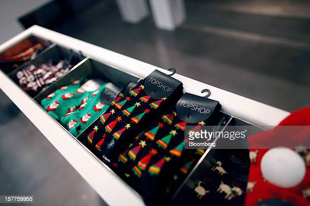 Logos sit on the tags of seasonal Christmas socks displayed for sale inside a Topshop store owned by Arcadia Group Ltd on Oxford Street in London UK...