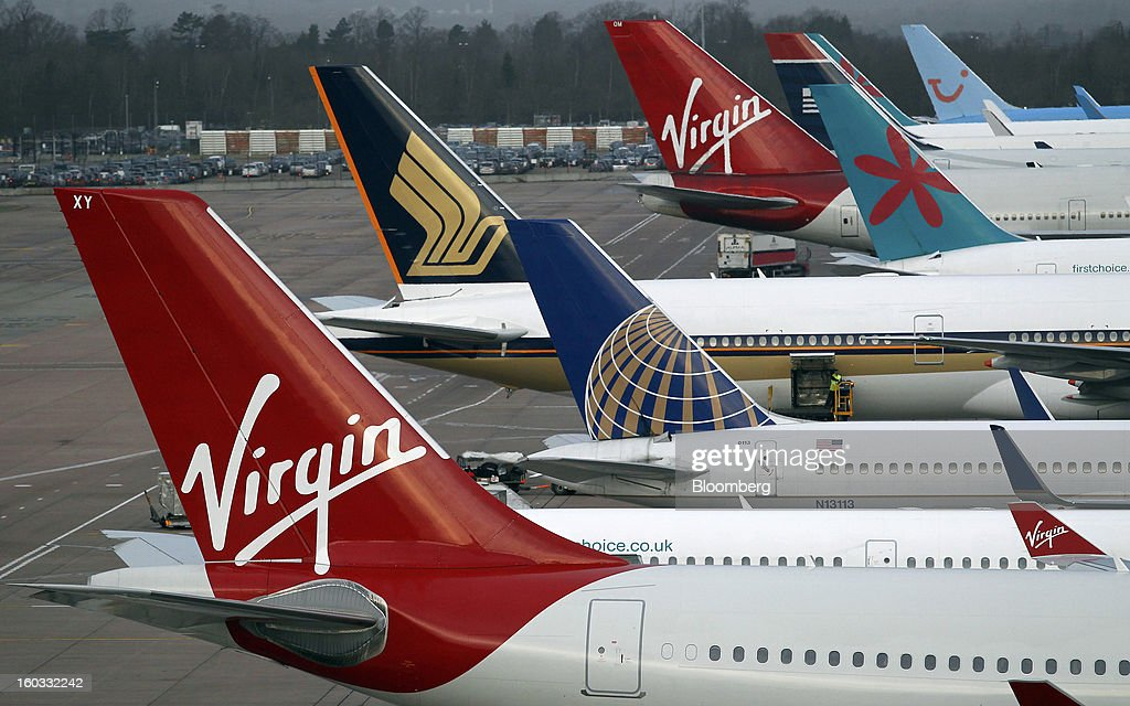 Logos sit on the tailfins of aircraft operated by Virgin Atlantic, United Continental Holdings Inc., Singapore Airlines, First Choice and Thomson Airways, sit parked at the gates of terminal two at Manchester airport in Manchester, U.K., on Tuesday, Jan. 29, 2013. Manchester Airports Group, owner of Britain's busiest airport outside London, is buying Stansted from Heathrow Airport Ltd., which is ceding 100 percent of Stansted to comply with regulatory requirements. Photographer: Paul Thomas/Bloomberg via Getty Images